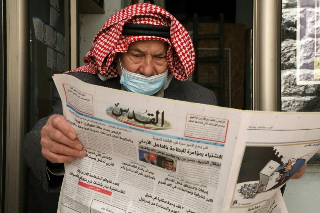 An elderly Palestinian man reads the daily newspaper Al-Quds, which published on its front page a story about the latest events in neighbouring Jordan