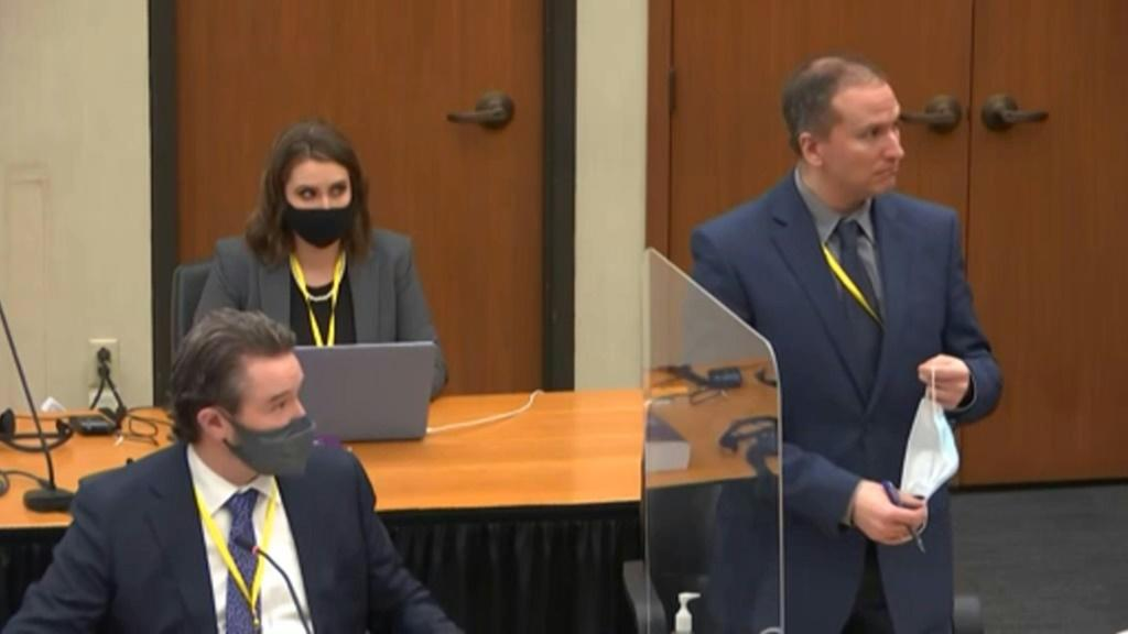Derek Chauvin (R) removes his mask in this screenshot obtained from pool video feed via Court TV