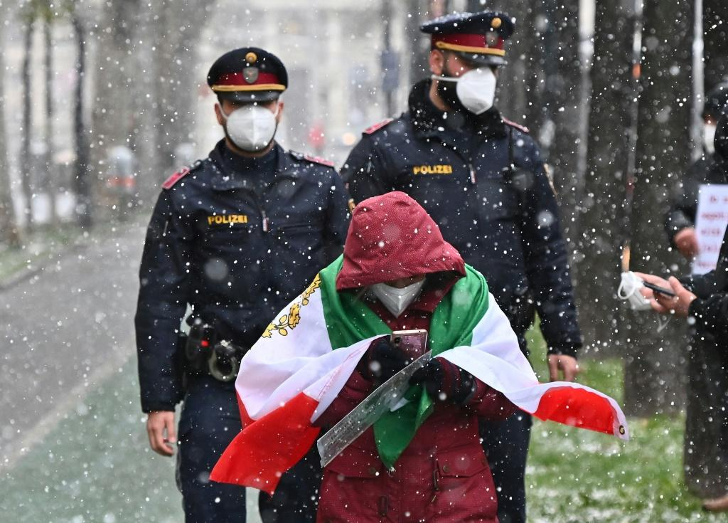 Policemen walk behind an Iranian opposition protester who took part in a rally against the Tehran government near the international Iran nuclear talks in Vienna