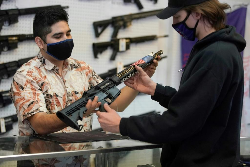 A customer looks at a custom made AR-15 style rifle at a shop in Orem, Utah in February 2021