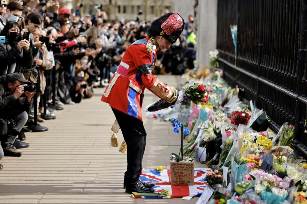 An ardent Royals fan lays a floral tribute at the front of Buckingham Palace in central London after the announcement of the death of Prince Philip