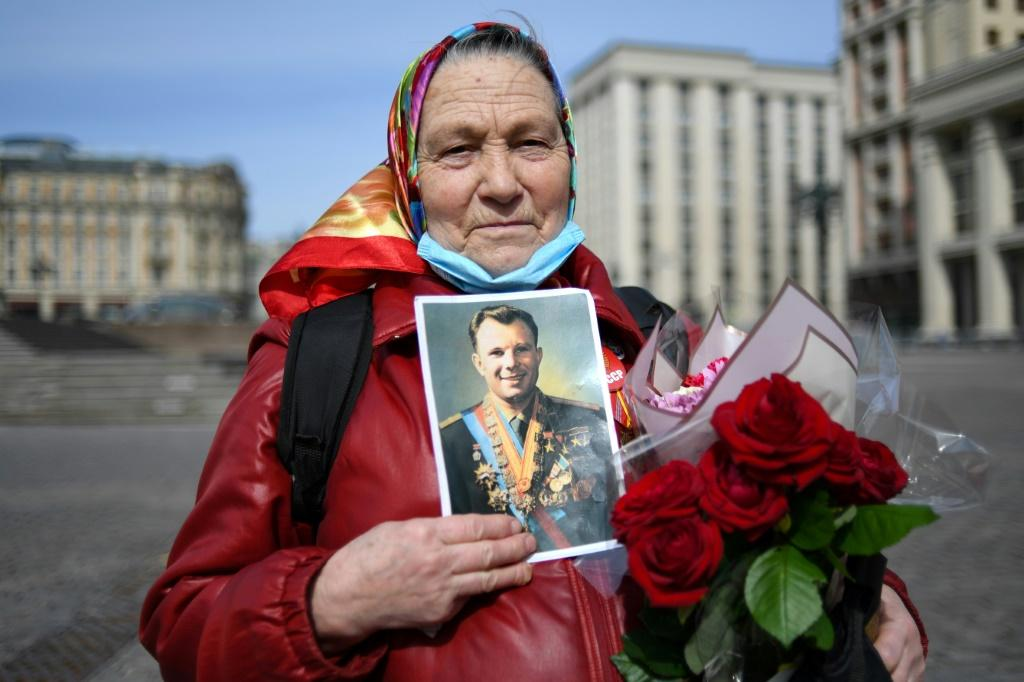 A Russian Communist party supporter holds a Gagarin portrait before attending a flower laying ceremony at the late cosmonaut's grave in Moscow