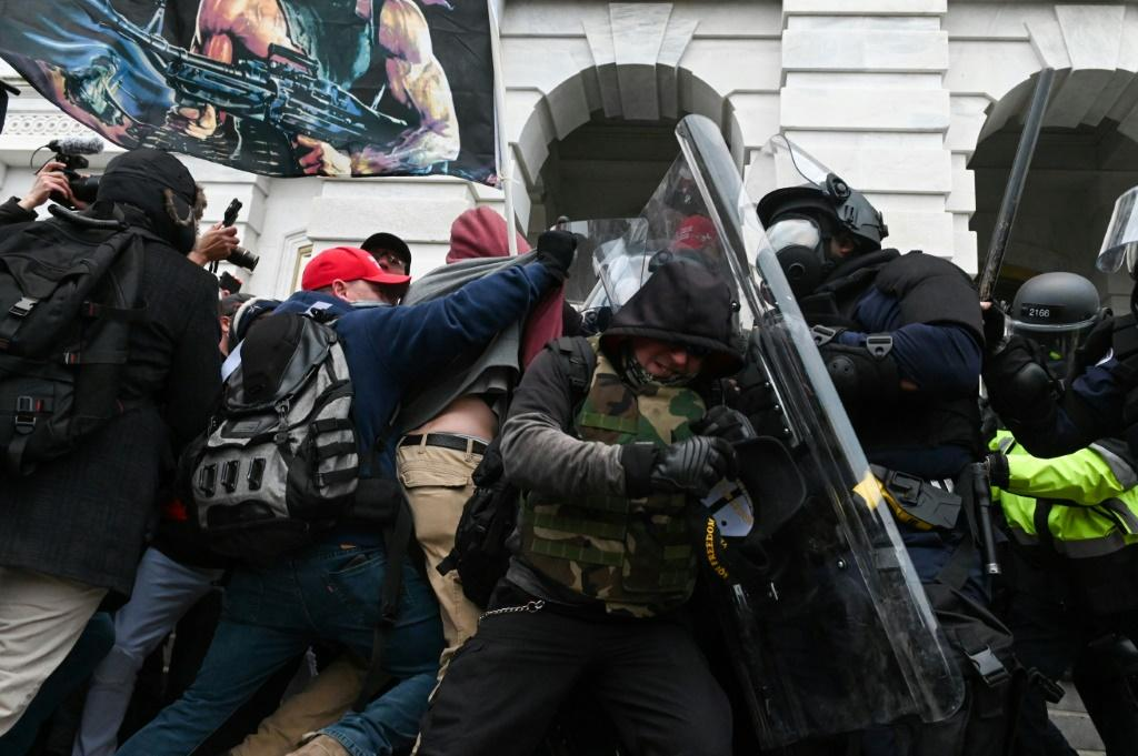 Riot police push back supporters of then-president Donald Trump on January 6, 2021 after they attacked the Capitol building in Washington