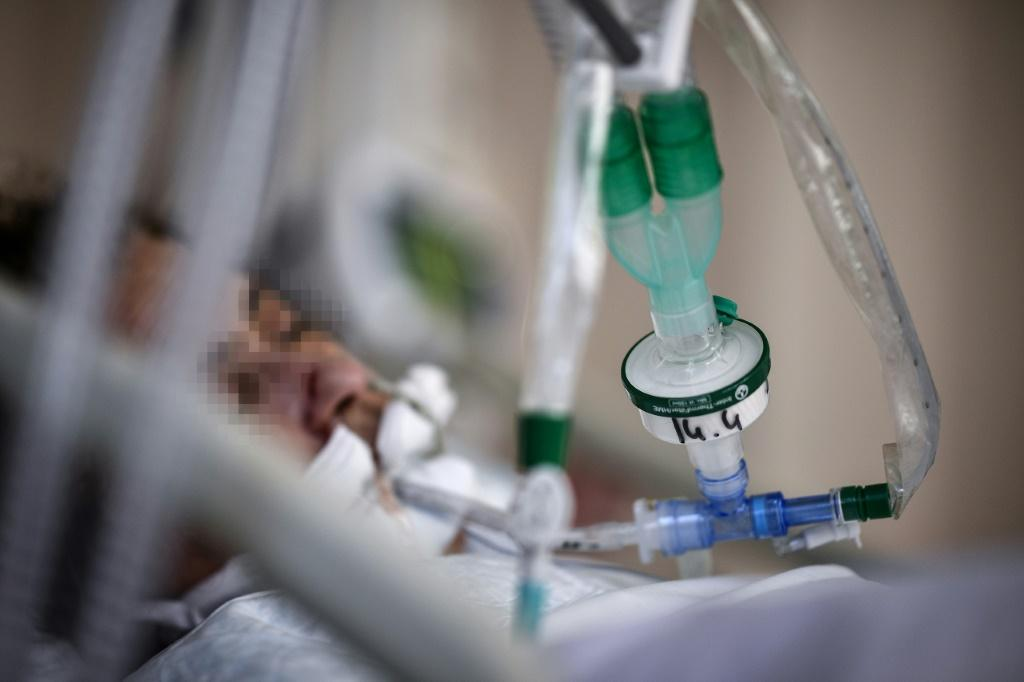 A patient infected with Covid-19 lays in a bed in the intensive care unit of the Saint-Camille hospital, in Bry-Sur-Marne, east of Paris