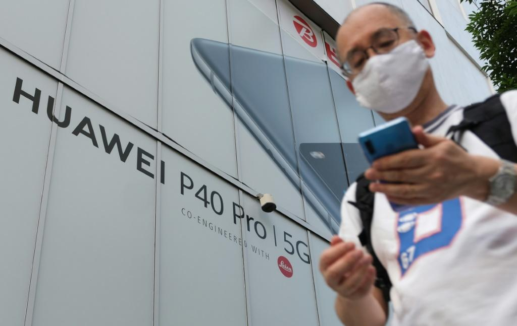 A pedestrian in Tokyo walks in 2020 under an advertisement for Chinese telecoms company Huawei, whose strength in 5G internet has alarmed the United States