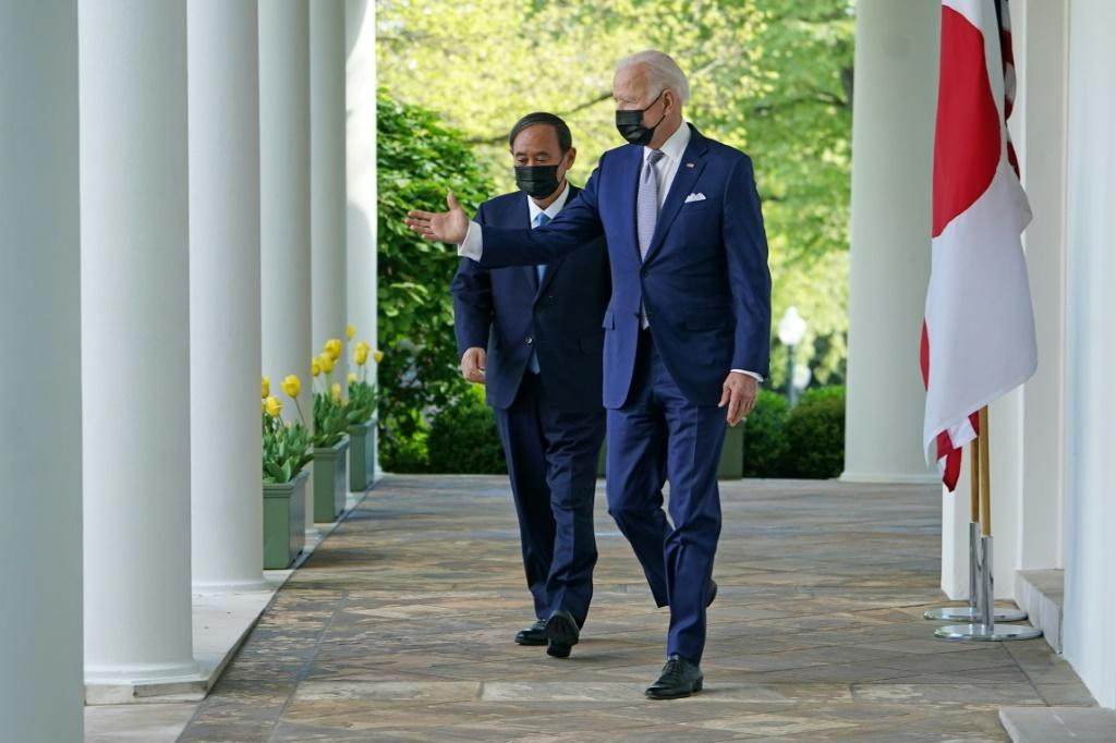 US President Joe Biden and Japan's Prime Minister Yoshihide Suga walk through the Colonnade to take part in a joint press conference in the Rose Garden of the White House