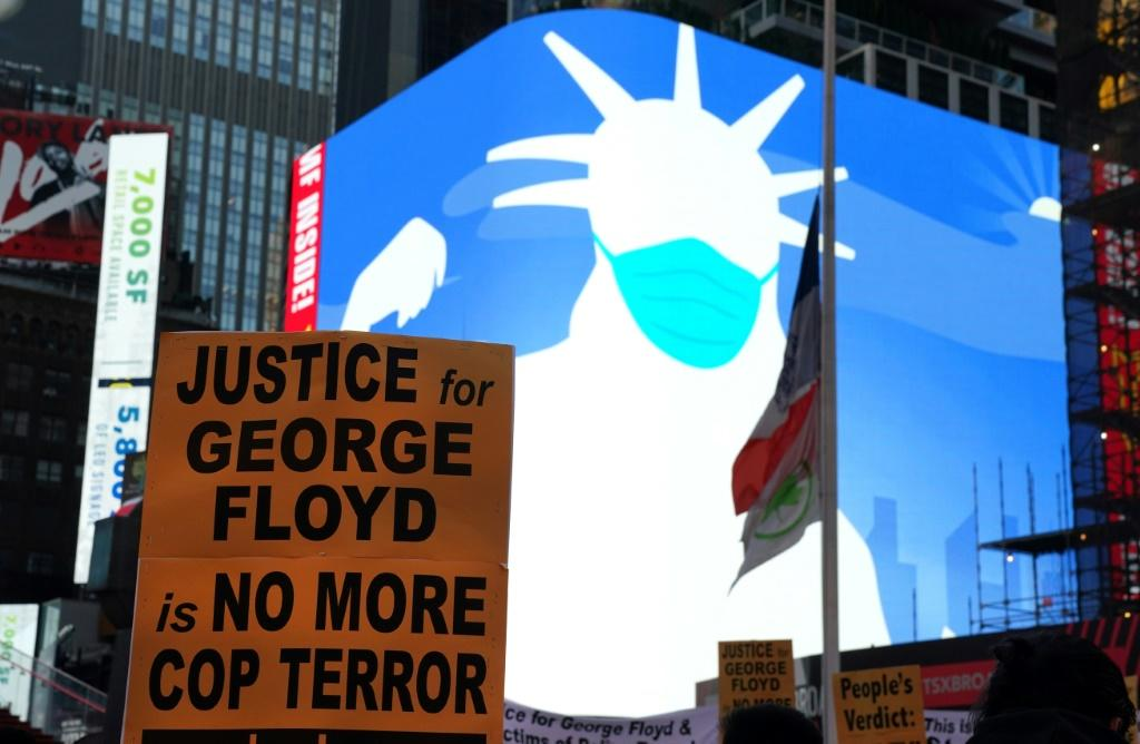A screen shows a silhouette of the Statue of Liberty wearing a face mask as people rally in Times Square in New York City after Derek Chauvin was found guilty on all counts in the murder of George Floyd