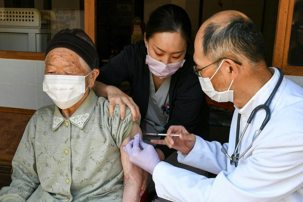 A health worker inoculates an elderly woman with a dose of the Pfizer-BioNTech vaccine in Japan's Nagano prefecture