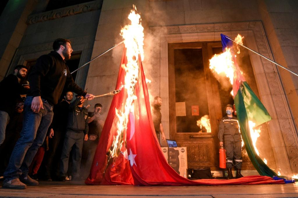 Men set fire to a Turkish national flag (L) and an Azerbaijan national flag in Yerevan, late on April 23, 2021, as Armenians mark the 106th anniversary of World War I-era mass killings. Armenians mark the 106th anniversary of the massacres in which they s