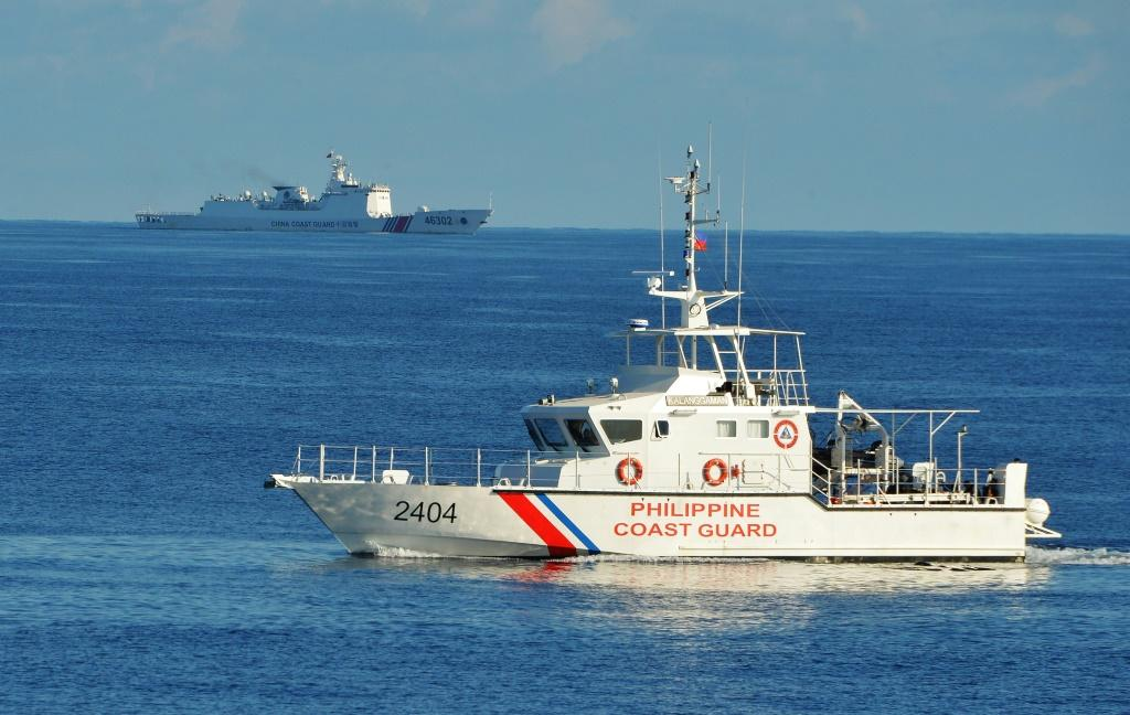 A Philippine coast guard ship sails past a Chinese coast guard ship near Scarborough shoal in the South China Sea in May 2019