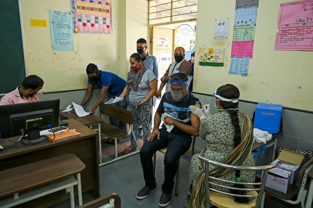 A health worker inoculates a man with a dose of the Covaxin Covid-19 coronavirus vaccine in a school-turned-vaccination centre in New Delhi