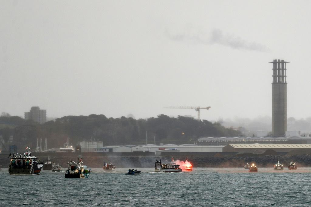 A flare is lit as French fishing boats protest in front of the Jersey port of Saint Helier on Thursday
