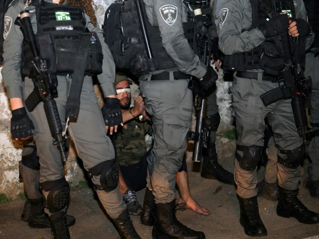 A Palestinian demonstrator is blindfolded and surrounded by Israeli security forces. Police say they made a total of 11 arrests.