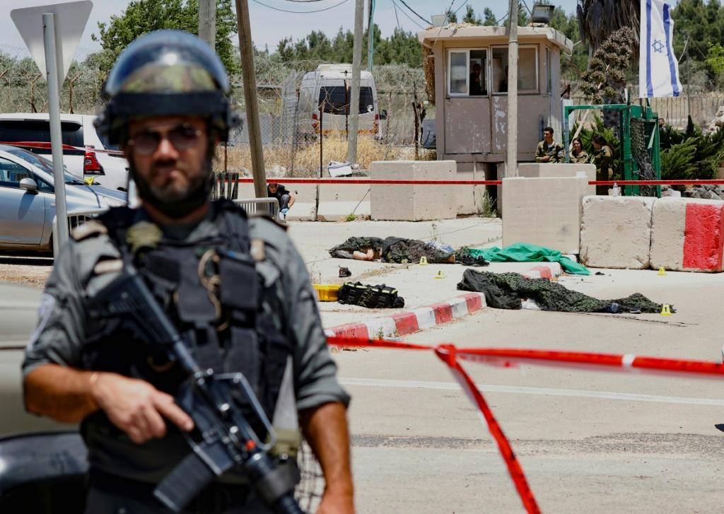 An Israeli soldier stands in front of the bodies of two Palestinians shot dead after they were reported to have opened fire on an Israeli base