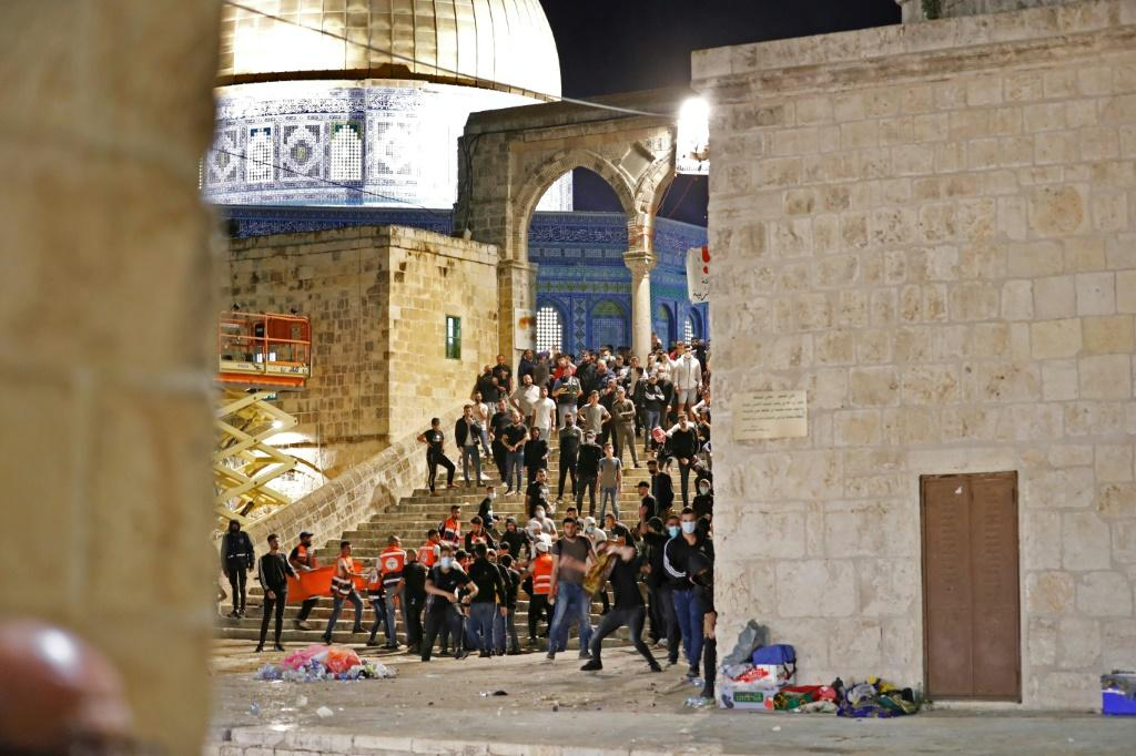 Palestinian protesters hurl stones during rare clashes with Israeli police at the Al-Aqsa mosque compound in Jerusalem, on May 7, 2021
