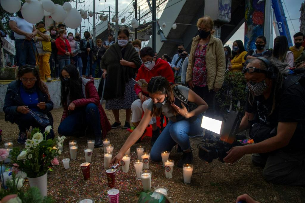 People light candles and place flowers at the site of a Mexico City metro rail accident that left 25 dead and sparked calls for justice