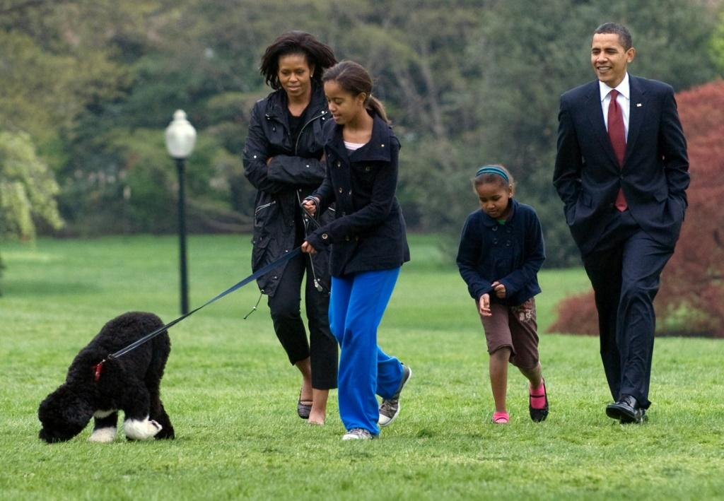 Malia Obama walks her new six-month old Portuguese water dog Bo alongside US President Barack Obama, Sasha Obama and First Lady Michelle Obama on the South Lawn of the White House in Washington, DC, on April 14, 2009
