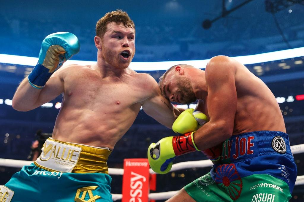 """Mexican champion Saul """"Canelo"""" Alvarez (left) throughs a punch at British boxer Billy Joe Saunders during their super middleweight title fight at the AT&T Stadium in Arlington, Texas"""