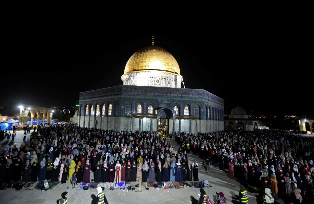 Palestinian faithful hold night-time prayers in front of the Dome of the Rock in the Old City of Israeli-annexed east Jerusalem