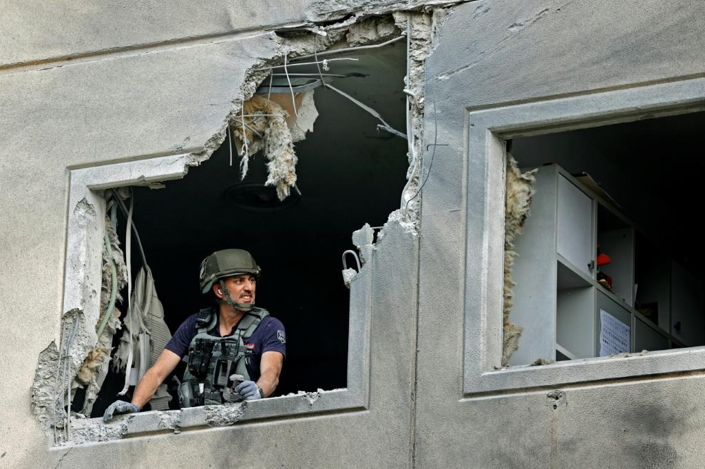 An Israeli sapper checks a damaged apartment in the southern Israeli city of Ashkelon after rockets were fired by the Hamas movement from the Gaza Strip towards Israel overnight