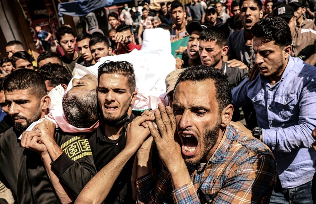 Mourners carry the body of Majd Abu Saadahthe, a Palestinian killed in an Israeli airstike, during his funeral in the town of Khan Yunis in the southern Gaza Strip