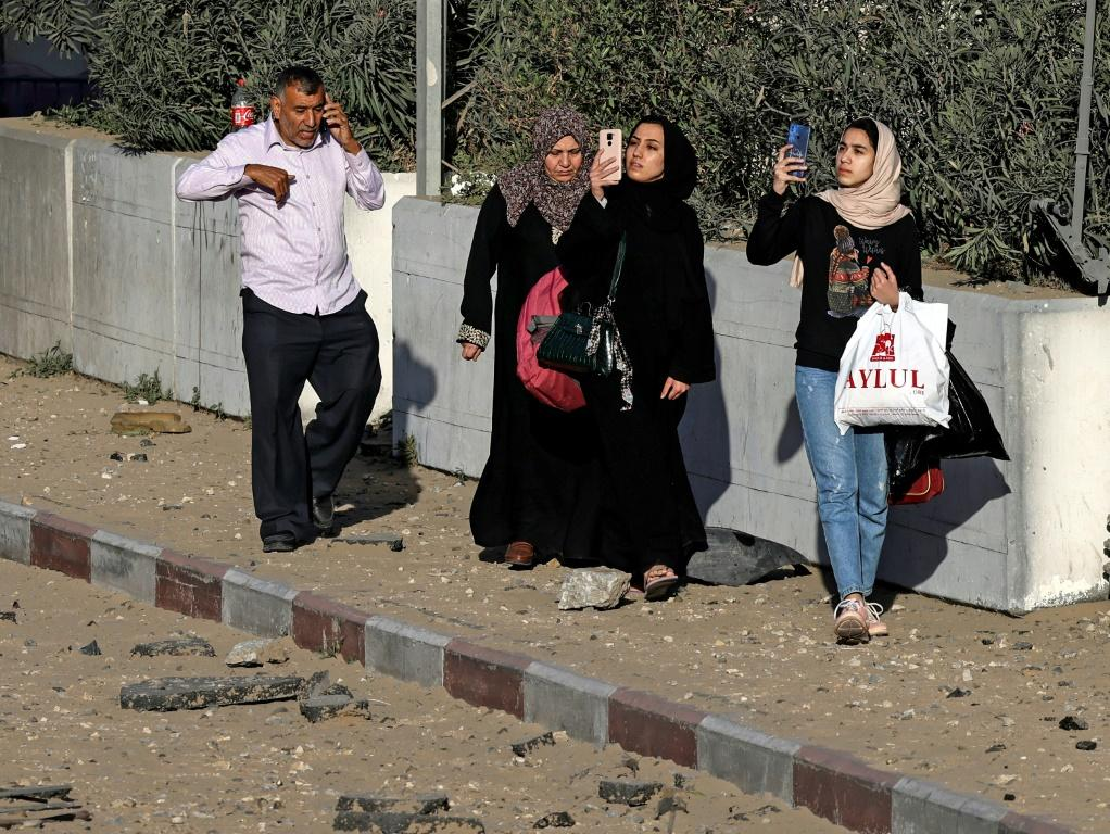 Palestinian women take photos of damaged buildings following Israeli airstrikes on Gaza City early on May 12
