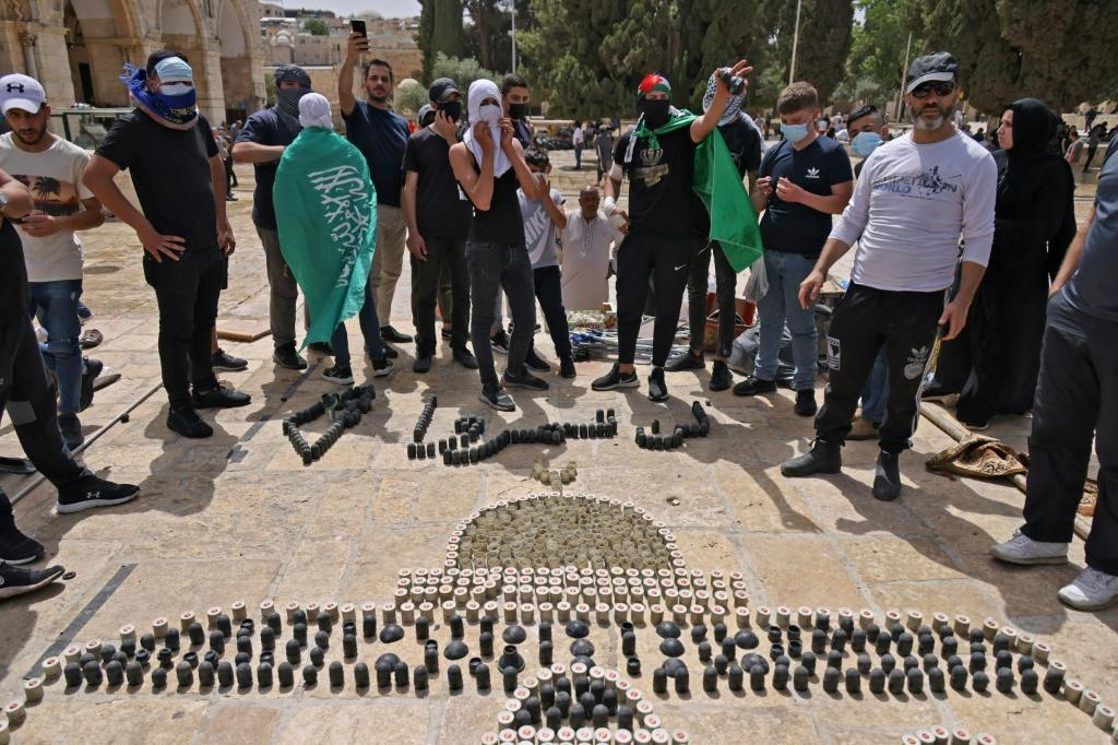"""Palestinians gather around an installation made with empty shells of stun grenades and tear gas canisters depicting the Dome of the Rock with the Arabic slogan """"you shall not pass"""", at Jerusalem's Al-Aqsa mosque complex on May 10"""