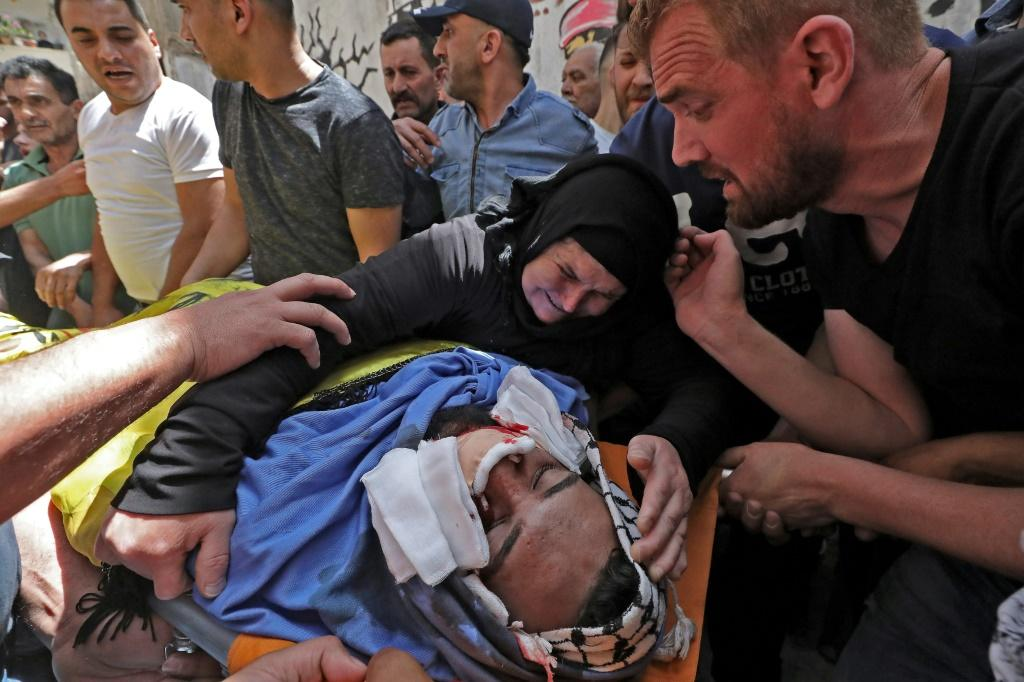 Relatives of Palestinian Hussein al-Titi, 26, killed by Israeli gunfire in Fawwar refugee camp near the city of Hebron, in the occupied West Bank, mourn over his body