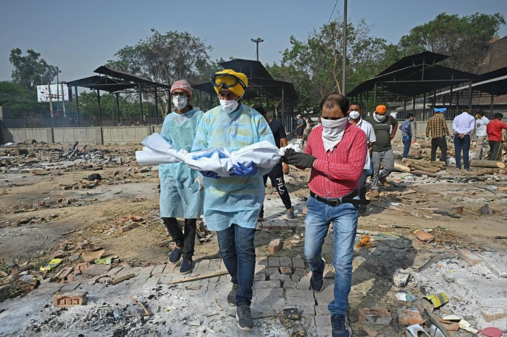 A volunteer carries the body of a child who died of Covid-19, at a crematorium in New Delhi