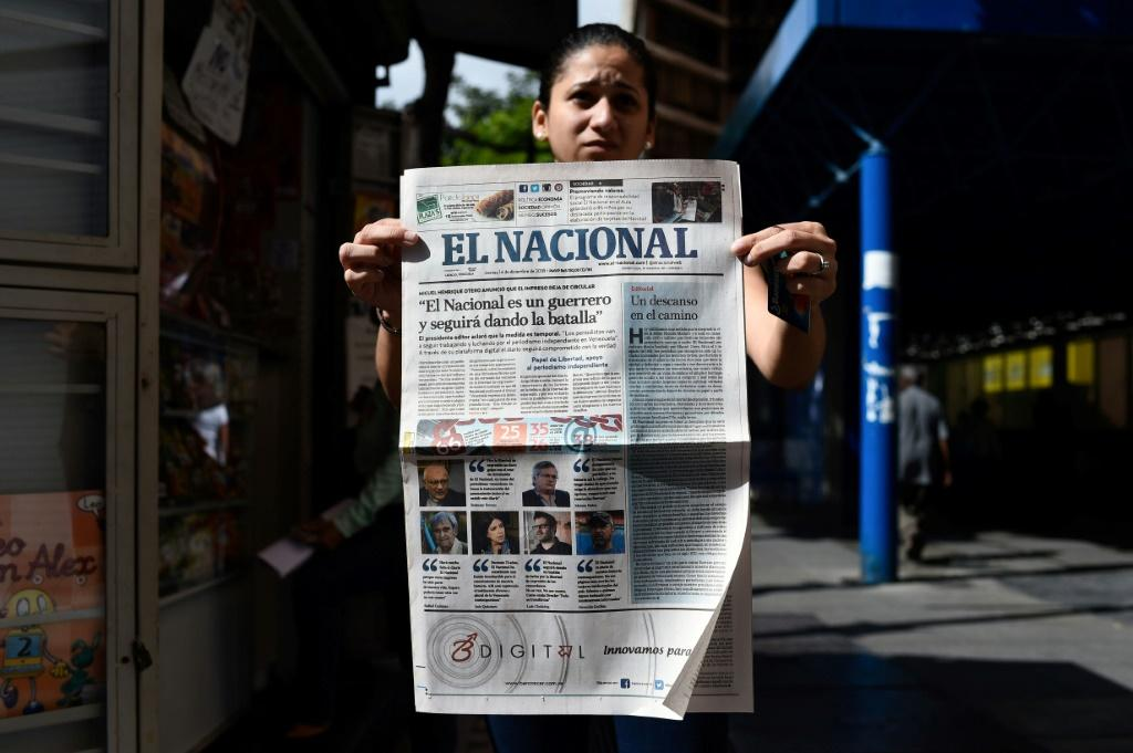 """A woman holds up the final printed edition of El Nacional on December 14, 2018, with its front page reading """"El Nacional is a warrior and will keep on fighting"""