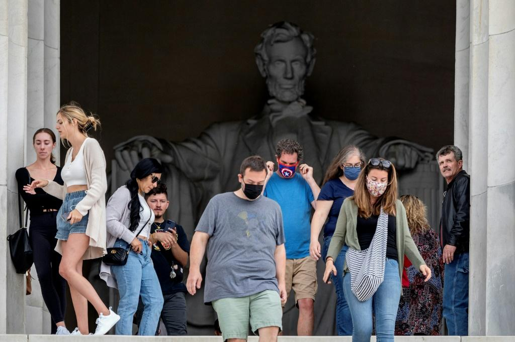 Some could still be seen wearing masks around Washington landmarks like the Lincoln Memorial Friday