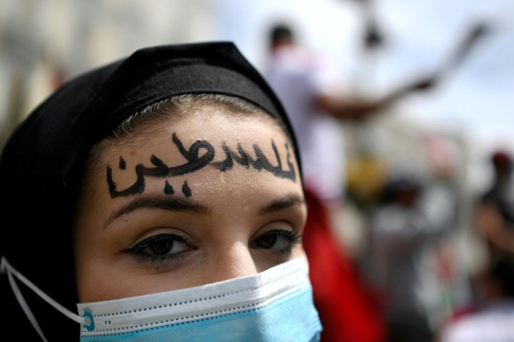 """A woman sporting the word """"Palestine"""" in Arabic marches in Madrid"""