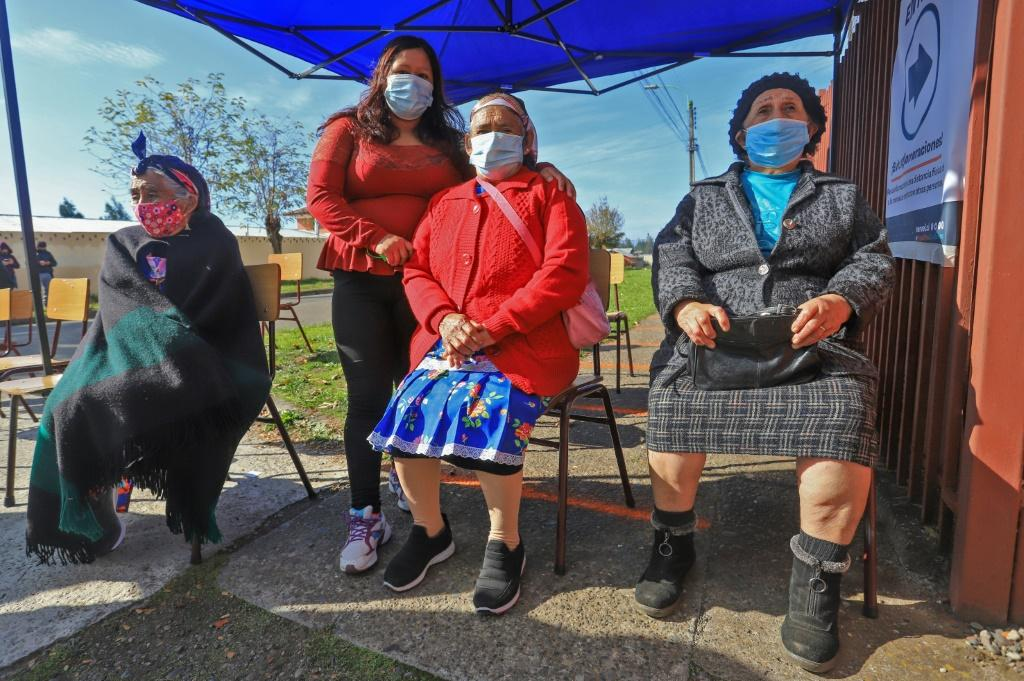 Mapuche indigenous women wait to vote during Chile's elections in Temuco on March 15, 2021