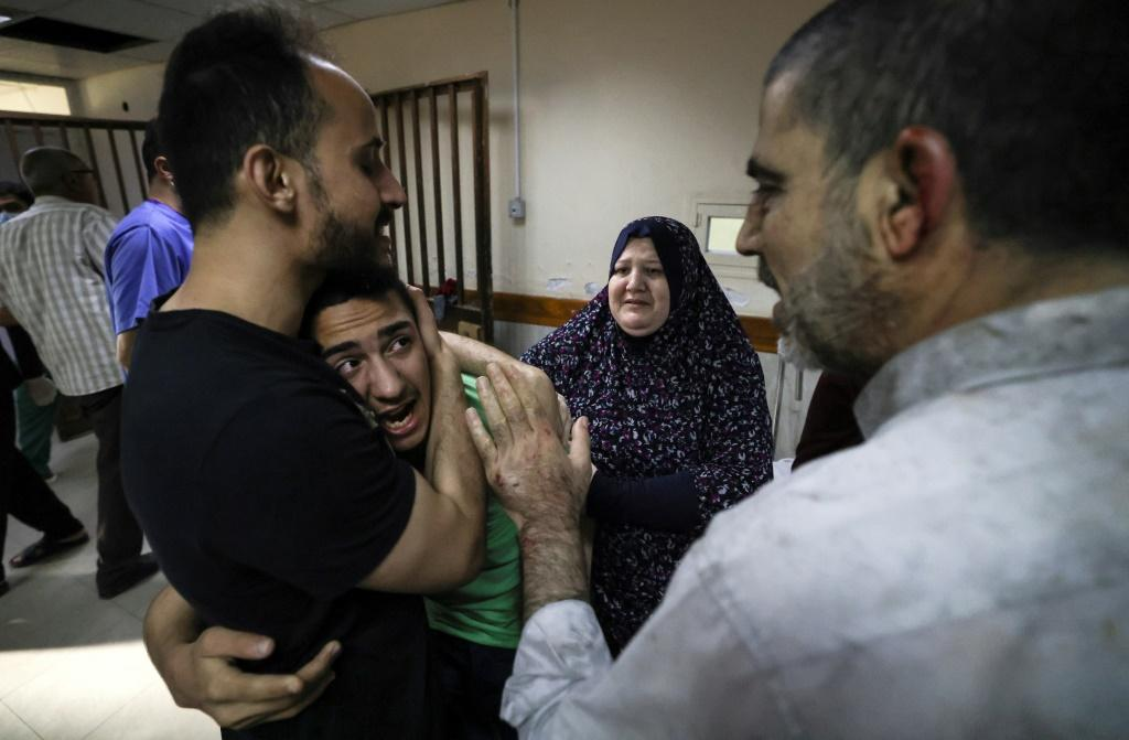 A member of the Abu Dayer family, surrounded by relatives, cries at the Al-Shifa hospital after the death of his father and cousin in an Israeli air strike on the family's home in Gaza City on May 17