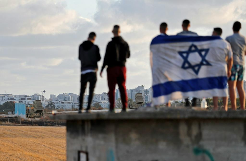 Israelis gather to watch the Iron Dome aerial defence system launch a missile to intercept a rocket launched from the Gaza Strip, above the southern Israeli city of Ashdod, on May 17