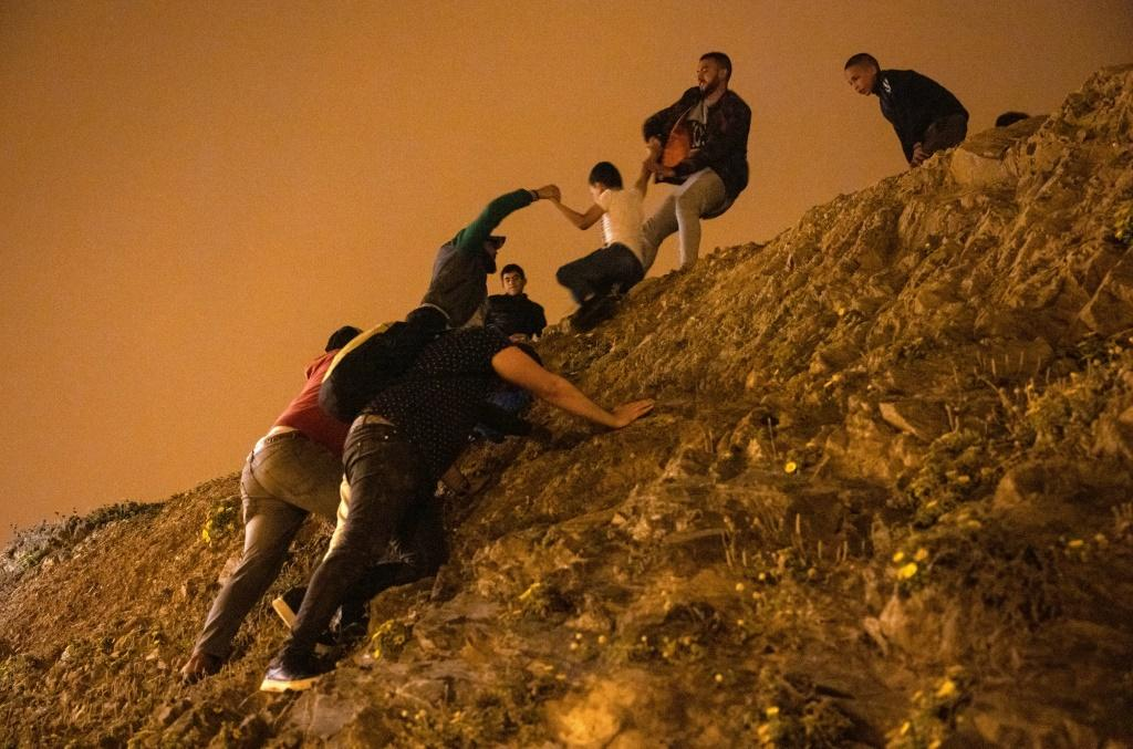 Moroccan migrants climb a rocky cliffside as a policeman watches in the northern town of Fnideq as they attempt to cross the border from Morocco to Spain's North African enclave of Ceuta on May 18, 2021.At least 5,000 migrants, an unprecedented influx at