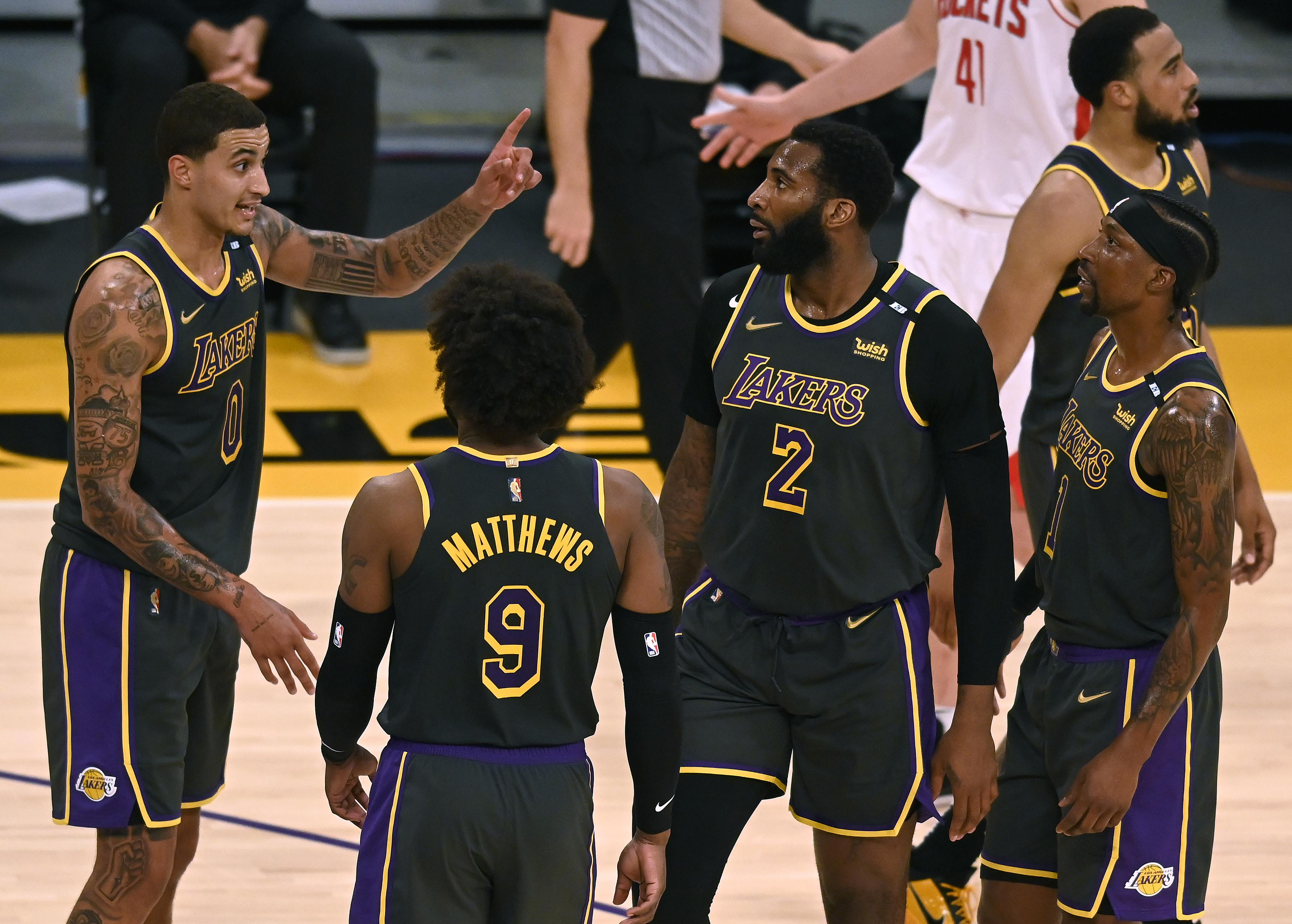Kyle Kuzma #0 of the Los Angeles Lakers talks to Wesley Matthews #9 Andre Drummond #2 and Kentavious Caldwell-Pope #1 after a stop in play against the Houston Rockets