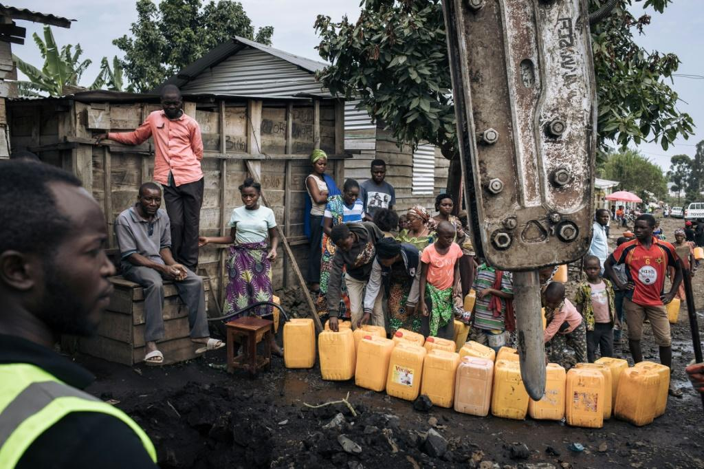 Goma residents collect water while workers repair power lines destroyed by the lava flow from the Nyiragongo volcano