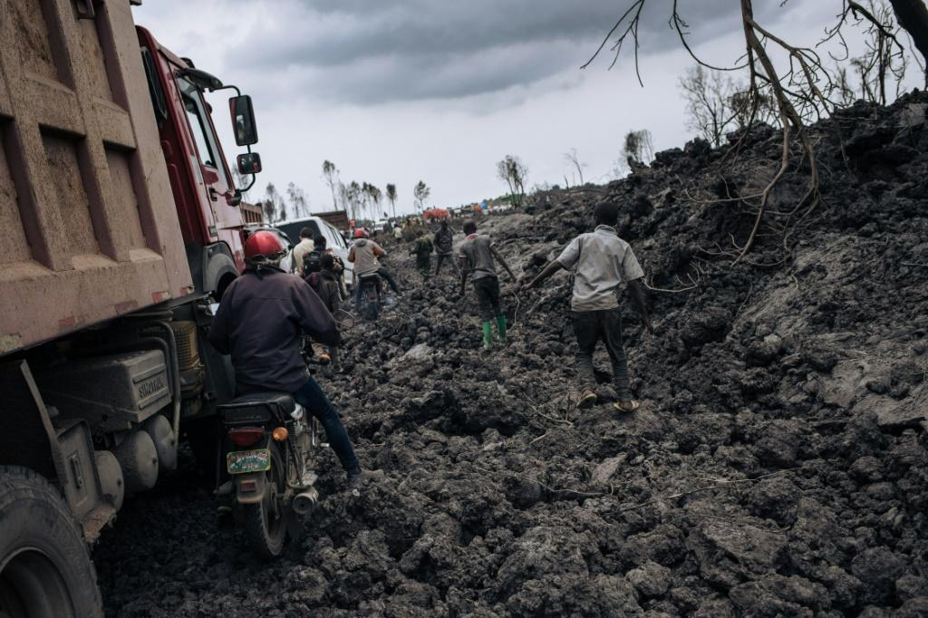 People try to make their way through solidified lava in the DR Congo city of Goma after last Saturday's volcanic eruption