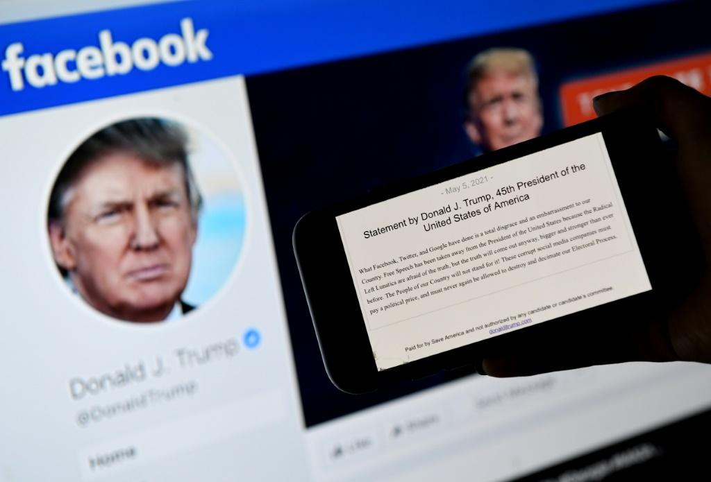 In this file photo illustration, a phone screen displays former US President Donald Trump's statement on the background of his Facebook page
