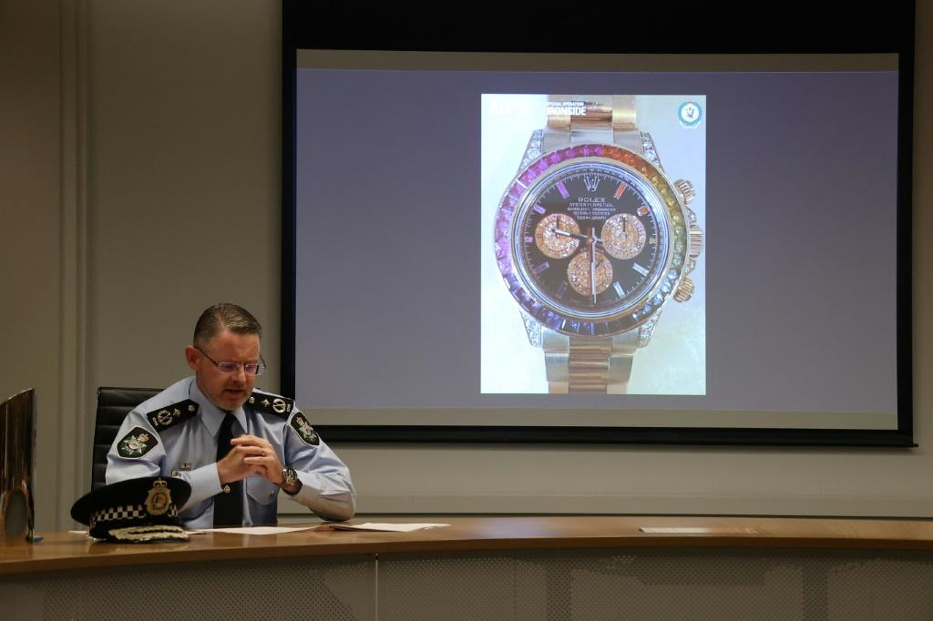 Australian police show a slide displying a seized gold and gemstone-studded Rolex watch, valued at $295,000