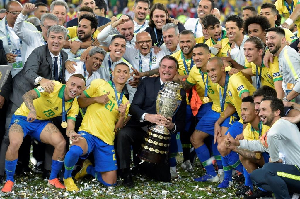 Brazilian President Jair Bolsonaro holds the Copa America trophy in July 2019 as the national team celebrate after winning the title in Rio de Janeiro
