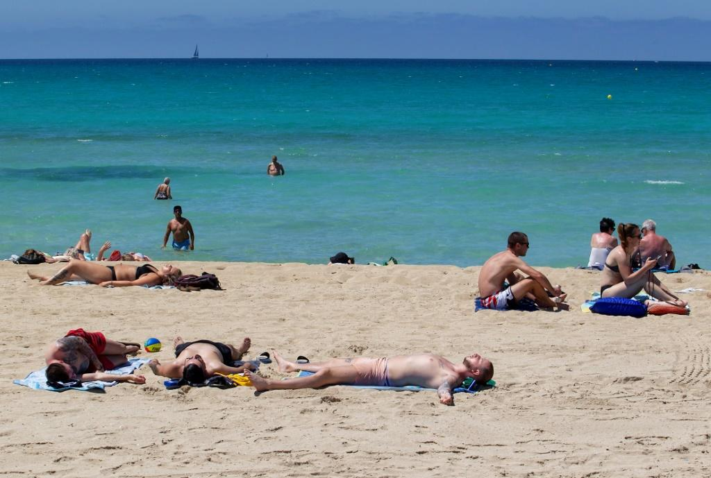 Tourists sunbathe at Palma Beach in Palma de Mallorca after Spain opens its borders to vaccinated travelers from all over the world