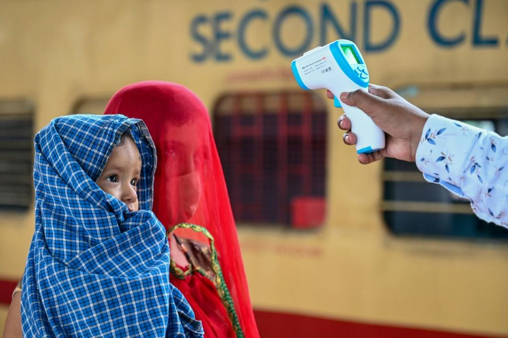 A child undergoes a temperature check at a railway station in Mumbai