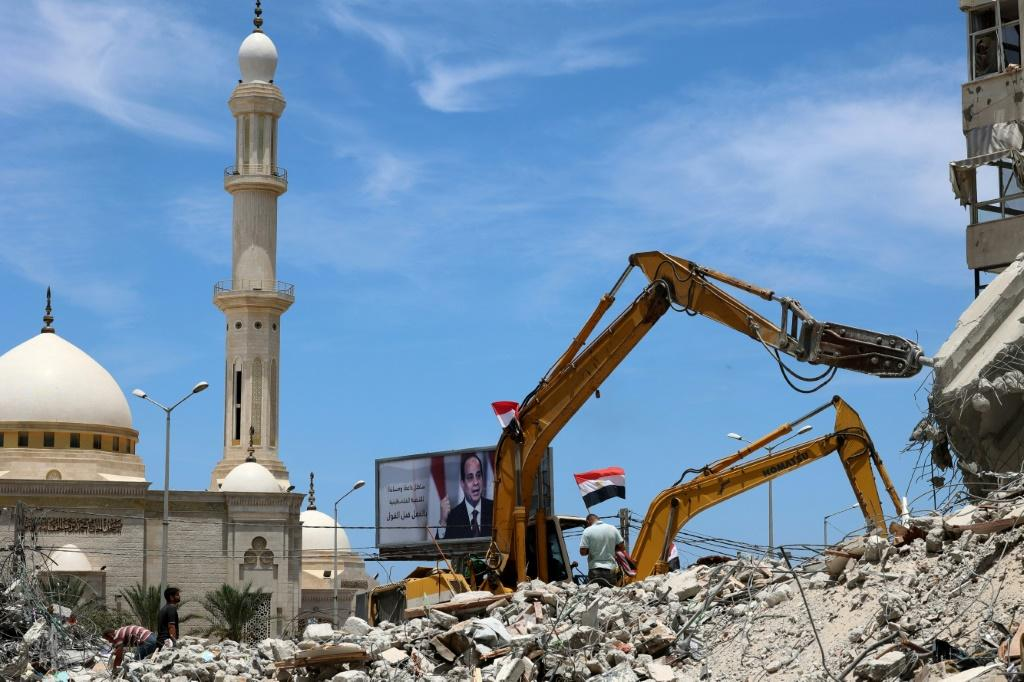 Egyptian workers use bulldozers to remove the rubble of Gaza City buildings destroyed by Israeli air strikes in this picture taken on June 8, 2021