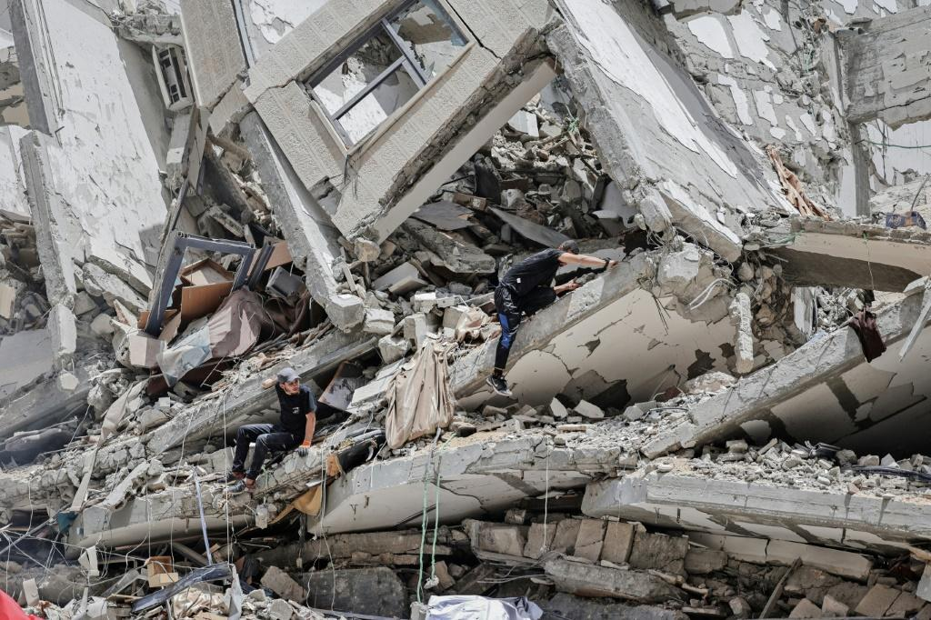Palestinian workers clear the rubble and debris in Gaza City's Al-Rimal neighbourhood, which was targeted by Israeli strikes in May