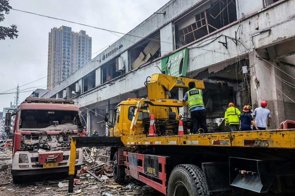 Workers search for victims in a building damaged by a gas line explosion in the Chinese city of Shiyan