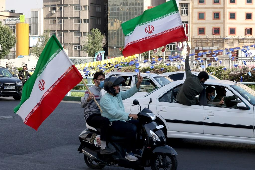 Iranians waving national flags drive past an electoral banner showcasing Iran's ultraconservative candidate Ebrahim Raisi during a street rally in the capital Tehran on June 15, 2021