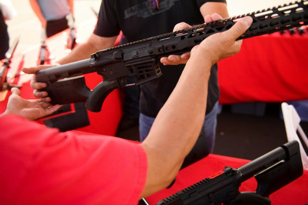 A clerk hands a customer an AR-15 style rifle from TPM Arms LLC on display for sale at the company's booth at the Crossroads of the West Gun Show at the Orange County Fairgrounds on June 5, 2021 in Costa Mesa, California