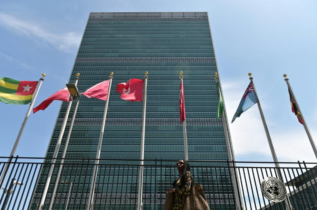 A person walks past flags outside the United Nations headquarters on May 20, 2021 in New York